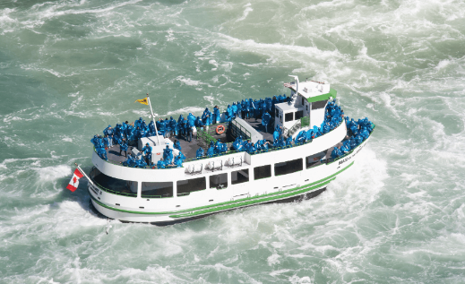 Maid of the Mist tour boat with tourist on board to see nearly Niagara's iconic Horseshoe Falls.