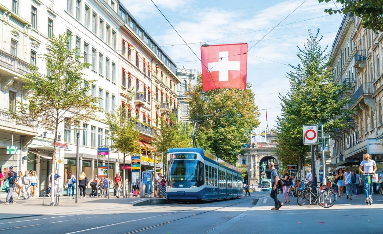 A tram drives down the center of Bahnhofstrasse while people walk on the sidewalks in Zurich City