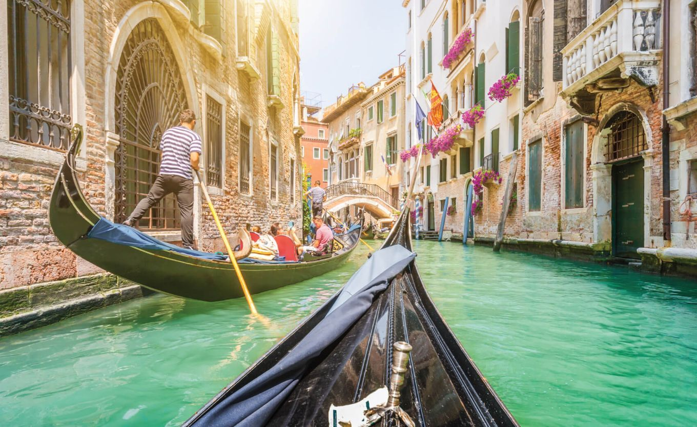 Traditional gondolas on narrow canal in Venice
