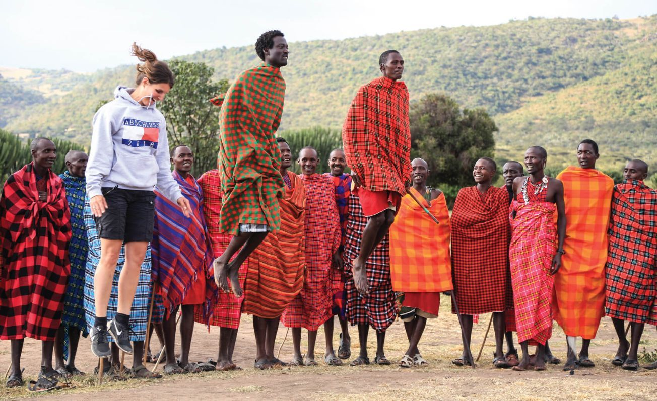 Tourist jumps with Masai warriors as cultural ceremony in Masai Mara Village, Kenya